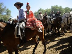 Members of the Triana brotherhood cross the Puente del Ajoli during the annual El Rocio pilgrimage in Huelva, Spain. Thousands of devotees in traditional outfits converge in a burst of colour as they make their way on horseback and decorated carriages across the Andalusian countryside