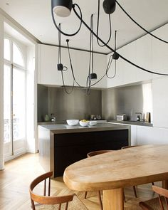 The kitchen is designed by Boffi. Aim pendant lamps by Ronan and Erwan Bouroullec for Flos hang above a table by Charlotte Perriand. The 1940s Grass-seated chairs are by George Nakashima