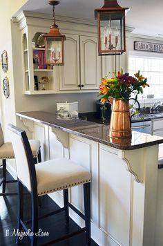 11 Magnolia Lane kitchen with creamy off- white cabinets, copper lanterns, and black and brown granite.