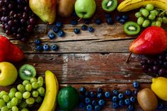 fruits - Mixed fresh fruits on rustic wooden board. Healthy eating background. Top view.