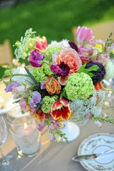 Some of the centerpieces will be white compote vases spilling with green hydrangeas, dark purple tulips, pink astrantia, seasonal greenery and orange spray roses.