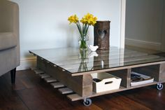 Handmade grey varnished coffee table, made from upcycled industrial pallets, with a glass top and casters