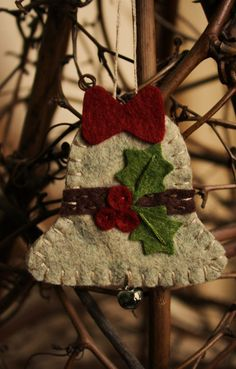 "A Holly Bell ornament made of felt. The Story or Symbolism:  Traditionally, bells are rung by carolers to announce their arrival, as they travel from door to door singing at holiday time.  This felt bell ornament is inspired by that tradition and brings with it the hope that love and joy will come to you.  By ""urbanpaisley"" on etsy."