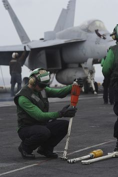 GULF OF OMAN (June 13, 2013) – Aviation Boatswain's Mate (Equipment) Airman Robert Cipollo (right) inspects catapult equipment on the flight deck of the aircraft carrier USS Nimitz (CVN 68). Nimitz Strike Group is deployed to the U.S. 5th Fleet area of responsibility conducting maritime security operations and theater security cooperation efforts. (U.S. Navy photo by Mass Communication Specialist 2nd Class Devin Wray/Released)