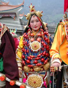 Tibetan woman from Nyarong in exquisite and heavy ceremonial finery from her area. She wears ornaments from practically head to toe, with many huge gaus hanging from her belt, several coral necklaces, many gold ornaments in her headdress, ivory bracelets on her wrists and big gold rings on every finger.
