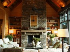 A massive stacked stone fireplace and rough-hewn pine mantel is the focal point of the media area.