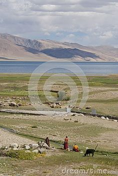 Buddhist monks looking at beautiful lake and mountians in Ladakh, Himalayas, India