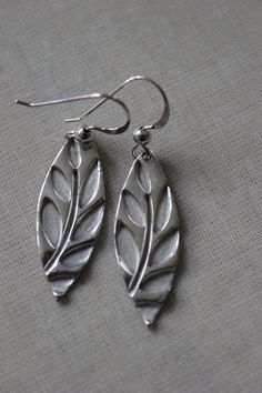 Handmade silver clay leaf shaped earrings featuring an embossed leaf design.