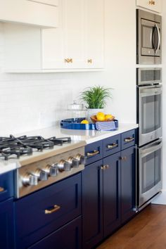 Bright blue cabinets bring a nontraditional yet fabulous flair to this kitchen. The space stays light and bright because of the white counters, cabinets and backsplash. A gas stove plus three ovens are a cook's dream.
