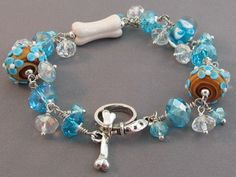 Dog bone bracelet with turquoise crystals and artisan lampwork beads.  Lots of pretty bling and a silver dog collar and dog bone toggle clasp.  Handmade by For Love of a Dog