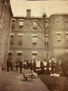 Staff at Colney Hatch Asylum wait for a patient to come down from a tree. Barnett, London. ca 1895.