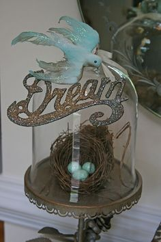 I bought this vintage hand dyed and glittered bird at the flea market...she perched on this cloche in my entry...