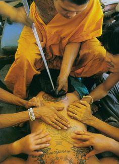 Monks practicing and receiving traditional hand-tapped tattoos.  These men have brass - it's incredible.