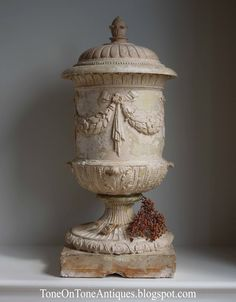 urn with beaded rim, draped laurel swags and pine cone finial