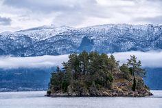 Island beneath the mountan - Small island beneath a mountain range deep in a Norwegian fjord