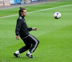 He's got skills: Styles shows off his moves on the pitch while concentrating hard...