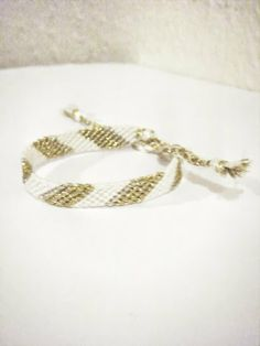 Diagonal Candy Stripe Friendship Bracelet by PrettyDroplets  This lovely bracelet is handcrafted from white and two shades of gold (glitter) embroidery floss in a diagonal striped pattern.  Perfect for everyday wear with a little glitz!