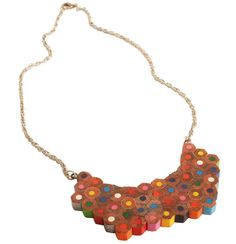 Silver coloured metal chain necklace with statement piece made up of recycled pencils in assorted colours. Uses trigger fastening. Length: 44cm Motif size: 8x4.5cm Made in India