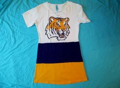 LSU Tigers game day dress: This LSU purple, gold and white dress is perfect for the Tigers fan who wants to show her spirit and tailgate in style! Size M/L  This loose fitted dress has a white distressed tshirt top with a great LSU Tiger logo. The purple and gold bottom is perfect! The cross tie at the top is adorable! It is available now in size M/L.  These unique dresses are original designs and handmade from gently used, up-cycled materials, primarily 100% cotton, with some 50/50 blends…