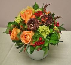 White glass vase with roses, viburnum, pincushion and other garden textures