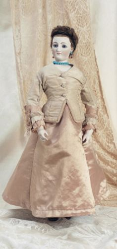 Fa'vours in Candlebeam Rooms: 50 French Bisque Poupee by Leverd & Cie 4 Bte SGDG (head) 4 FG (shoulderplate). Comments: Leverd & Cie,circa 1869; Leverd_s wig system was deposed in May 1869. Value Points: extremely rare poupee retains her original brunette mohair wig as presented by the maker to illustrate his patent concept; the rarity of the model is rivaled only by her beauty.
