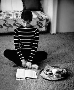 While filming the movie Sabrina, Audrey Hepburn rented an apartment on Wilshire Boulevard in Beverly Hills. Photographer Mark Shaw captures this intimate moment of a young Audrey at her apartment enjoying a snack while reading a book, 1953.