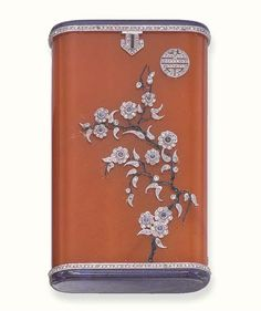 AN ART DECO AMBER, LAPIS LAZULI AND DIAMOND CASE, BY LACLOCHE FRERES. The oblong amber case applied with rose-cut diamond and cabochon sapphire blossoms with black enamel stems and diamond-set Chinese symbol, to the lapis lazuli terminals enhanced by rose-cut diamond borders (amber cracked to one corner), circa 1925