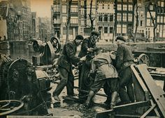1937. Scrap metal vendors dealing with iron machine parts at the Waterlooplein flea market in Amsterdam. In the background the Groenburgwal. #amsterdam #1940 #Waterlooplein #Groenburgwal
