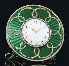 A SILVER-GILT AND GUILLOCHÉ ENAMEL DESK CLOCK BY FABERGÉ, WORKMASTER'S MARK OF HENRIK WIGSTRÖM, ST PETERSBURG, 1903-1904 Circular, enamelled in translucent green over a wavy sunburst guilloché ground applied with continuous scrolling band of laurel, centring a white enamel dial within a seed-pearl bezel, black Arabic chapters and pierced gold hands, all within a gadrooned border.