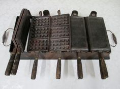 """Cast Iron Waffle Iron by CGMGallery $925.00. This antique Wagner Manufacturing Company (Wagner Ware) cast iron commercial waffle iron weighs in excess of 24 pounds. It is 26"""" in length from the outside of handle to outside of handle, 14 7/8"""" from back to front, and 3"""" in height. The base is 21 1/4"""" in length and 10 1/4"""" from back to front. Each of the 3 3/4"""" length wood handles are intact, somewhat warped, and the far right upper handle is split. Can you imagine using this baby?"""