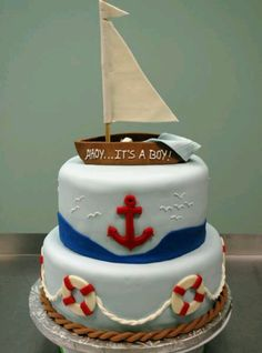 Nautical baby shower cake.  There's a sleeping baby in the boat!