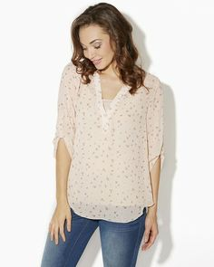 Tiny flowers bloom on this sheer chiffon blouse. V-neck with double-button placket. Long sleeves that can be rolled and fastened with a button tab. Shirttail hem that dips lower in back.