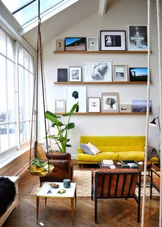 Gallery wall shelving and a bright yellow couch.