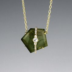 """This unique Jemma Wynne necklace features an asymmetrical slice of green tourmaline with diamond overlay that gives off just the right amount of sparkle. The pendant sits inline with an 18k yellow gold 16"""" chain."""