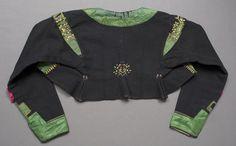 """Mörkblå vadmalströja garnerad med gröna sidenband och broderier. Tröjan har rund ringning fram, skört bak och axelkarm på ärmen. Tröjan är dekorerad med 50 mm breda gröna sidenband längs halsringning och ringning fram, längs nederkanten på framstycke och ärm samt på ärmkarmen. Ovanför ärmsprundet har ett kryss av banden sytts på, ovanför sitter en rosa """"ros"""" i siden. Dekorativa broderier i plattsöm, kråkspark och flätsöm på och invid de gröna banden på framstycken, ärmar och ärmkarmar samt…"""