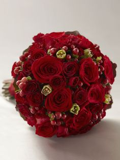 This red wedding bouquet is an expression of true love and rich romance. Red roses, spray roses, carnations, hypericum berries and galax leaves are accented with gold pixie pearl pins and tied together at the stems with a red satin ribbon to create a dramatic look perfect for your wedding day.