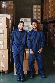Two young coworkers standing in a warehouse.  by BONNINSTUDIO for Stocksy United