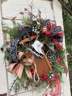 This Beautiful Christmas Wreath is made on a Pine Base. I have Layered it with Long Needle Pine, Icy Pine, Lots of Sparkly Red Berries, White and Red Sparkly Berry Branches, and Silver Pine. There is the Prettiest Rustic Looking Sled that I added and to that Some Ornamental Ice Skates. The Wreath is Finished out with A Chalkboard Style Ribbon with Christmas Sentiments, a Christmas Plaid, a Sheer Red Ribbon with Glittered Lines, and a Rustic Ribbon in Red and Green Stripe. All of the Ribbons…