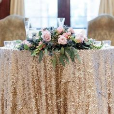 Sweetheart table featuring a gold sequin linen and large floral arrangement across the top with pink roses | Leslie Ann Photography | villasiena.cc