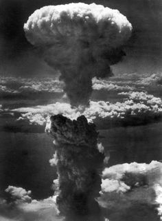 Dense column of smoke capped by mushroom cloud rises more than 60,000 feet into air over Japanese port of Nagasaki, result of atomic bomb, second ever used in warfare, dropped on industrial center from US B-29 Superfortress. August 8, 1945.