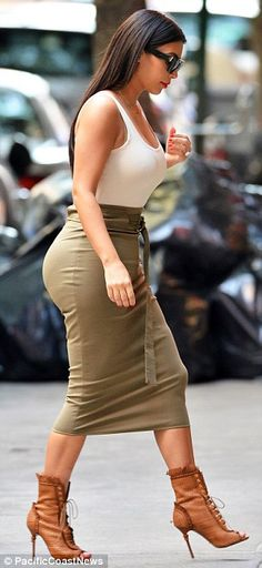 Kim Kardashian wore a tight olive green midi-skirt with tie waist, paired with a simple white tank top and calf-length leather lace-up peep-toe booties for a day out in NYC http://dailym.ai/1p9pLcj