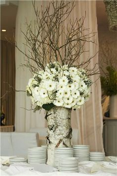 Birch bark covered vase and curly willow add rustic touches to a traditional white floral arrangement