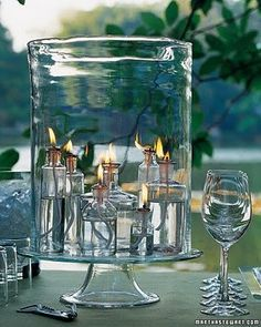 High impact with mini oil lamps made from small apothecary bottles placed in a glass hurricane