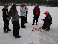 Properly setting a tip-up is critical for catching those cautious fish. Here the women are learning the proper technique. Great group of ladies taking an ice fishing class, Women's Outdoor Learning Center. Pickerel, Bass, Hornpout, Crappie, Bluegill.