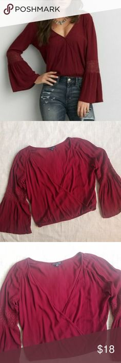 American Eagle Burgundy Wrap Top Flared Sleeves M Oversized burgundy wrap top with lacey detailed flared bell sleeves and elastic waist by American Eagle. Excellent preowned condition, no flaws seen. Size medium. American Eagle Outfitters Tops Blouses