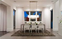 This Vancouver dining room has tile flooring, plush carpeting, sleek dining table and chairs, floor-to-ceiling curtains and a rectangular hanging light fixture.