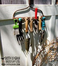 An old rake is just right for hanging up garden tools.