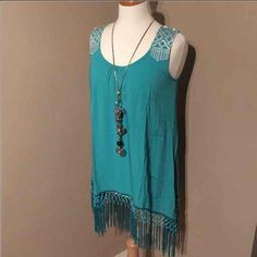 Boho chic fringe summer tank shirt. Beautiful spring/ summer  tank shirt.  Medium Turquoise with white ornate stitching on the shoulder straps.  Fringe along the bottom all the way around.  Beautiful color and addition to your spring wardrobe.  Looks great with a pair of black leggings.   Brand new. Never worn.   Please visit my page and see my other items.  Follow for future posts  For necklace and leggings. See my other posts. Tops Tank Tops
