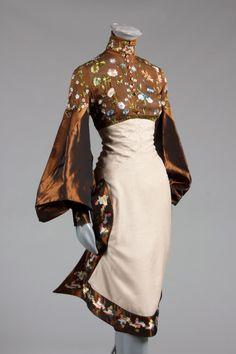An Alexander McQueen for Givenchy couture wildflower embroidered gown, probably Autumn-Winter 1999. The brown bodice with Lesage embroidery of blossom and foliage, tiny glass buttons from neck to waist front and back encasing dried flower sprigs, the skirt of fine brown and ivory houndstooth check with curved satin edges embroidered with ikat-like motifs, gigot sleeves of brown taffeta.