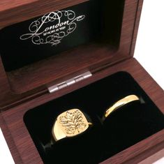 yellow gold signet ring with a seal engraved family crest and an yellow gold band by LONDON ENGRAVER